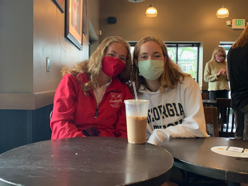 Leslie Baker '24 and Anna Hvidsten '23 sit in Starbucks with their coffee.