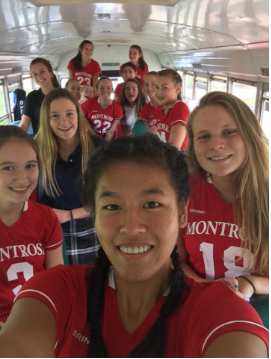 Field Hockey team poses for picture on the bus before the game.