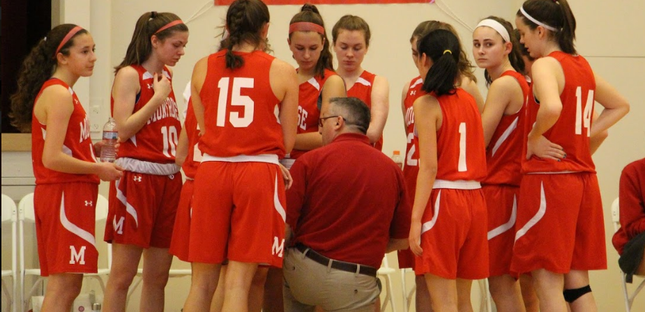 Varsity Basketball team huddles during Senior Game against Landmark on February 13th.