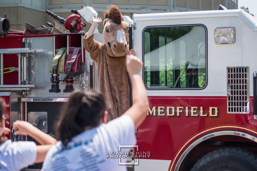 Montrose Mascot Monty waving at seniors from a Medfield firetruck.