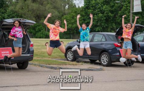 Four seniors jump for joy at the Senior Motorcade on May 29, 2020.