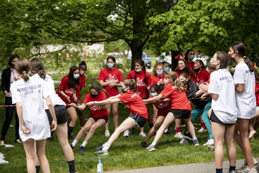 Red and white teams competing in tug of war during Field Day 2021.